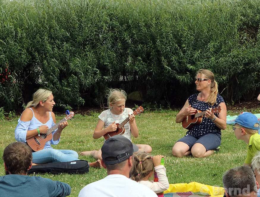 Musikschulkinder spielen Instrumente auf einer Grünfläche