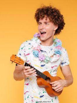 Ein Mann trägt ein Blumenhalsband und spielt Ukulele