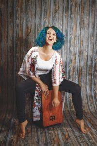 Eine Frau mit blauen Haaren spielt Cajón