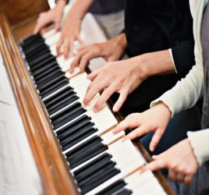 Viele Hände spielen auf einem Klavier
