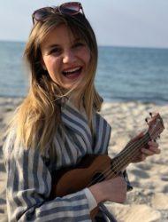 Musikschullehrerin Sandra Becker steht am Strand und spielt Ukulele