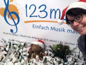 Musikschulleiterin Katharina O'Connor präsentiert vor dem 123musik-Logo viele Weihnachtsgeschenke