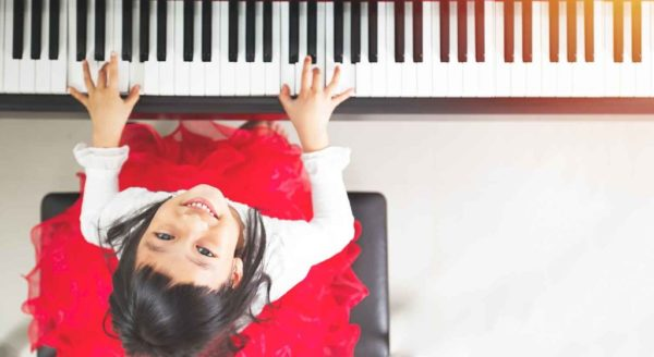 a girl is playing the piano and smiling