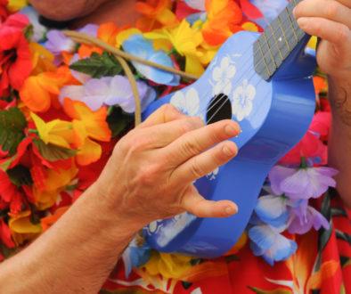 A man playing a Hawaiian ukulele wearing a bright flowered shirt
